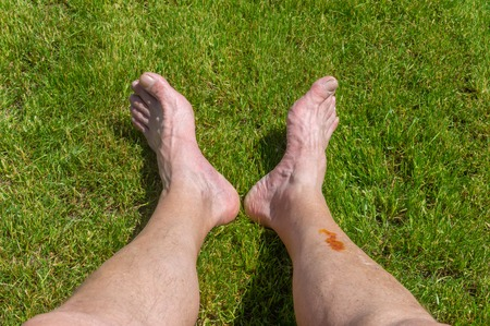 Ältere Füße, die auf einem grünen Rasen liegen, während sie sich nach einer langen Fahrradtour ausruhen