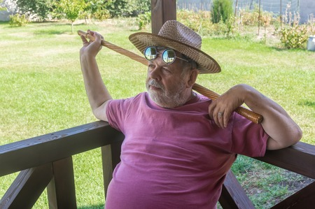 Portrait of happy bearded senior man in round sunglasses resting while sitting on veranda at summer season Stok Fotoğraf - 123098573