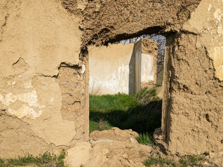 Window in ruined old clay-walled Ukrainian house closeup