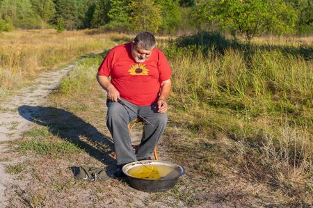 Old Caucasian senior man man fishing in ancient basin thinking he's still a kid