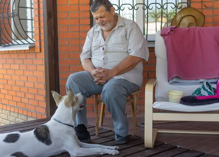Bearded senior talks to dog sitting near his house. The dog listen him with consideration.