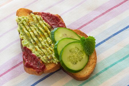 Toast with guacamole, spicy raspberry mash, slices of cucumber and flavored with mint