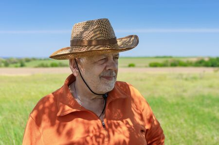 Portrait of bearded Caucasian senior farmer standing against green agricultural field and looking forward