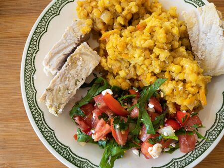 Top view on a plate with red lentil, tomato salad and slices of steamed pork