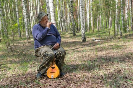 Seniors playing music on woodwind instrument sopilka while sitting on a stool in birch forest