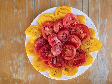 Top view on plate full of sliced red and yellow tomatoes and flavored with black pepper