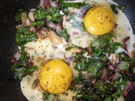 Top view on a pan with two fried eggs on stew onions and leaf beet Stock Photo