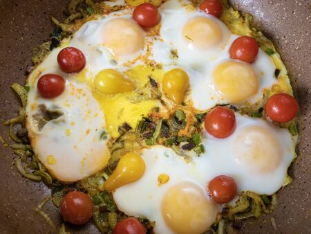 Pan full of eggs fried with vegetable, including onion,red and yellow cherry tomatoes and celery stem Stock Photo