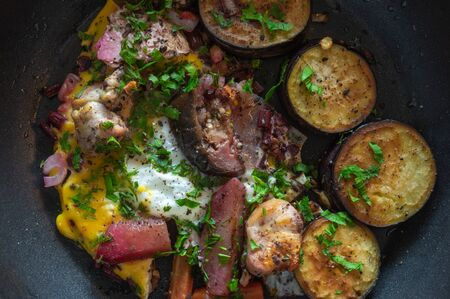 Top view on frying pan with vegetables, egg and pieces of turkey meat