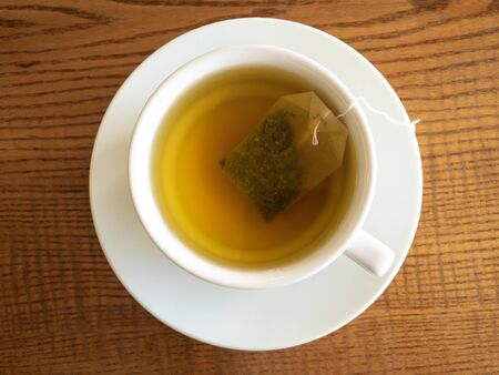 Top view on white porcelain cup on a saucer with green tea-bag inside standing on a wooden surface