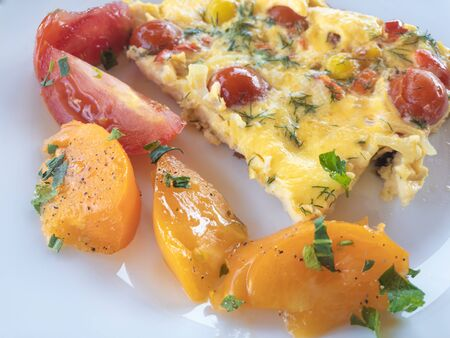 Close view on white plate with omelette and sliced yellow and red tomatoes Stock Photo
