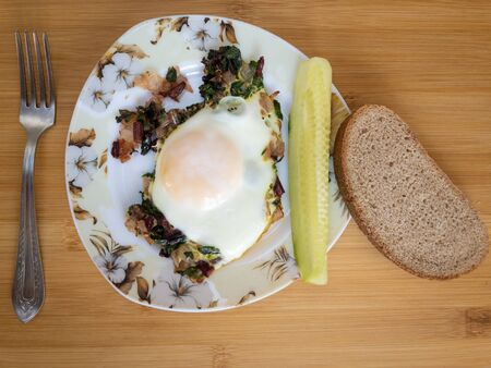 Top view on plate with egg fried on onion and mangold, slice of cucumber, brown bread and lonely fork Stock Photo