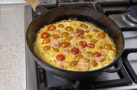Frying pan full of omelet with cherry tomatoes and sausage slices standing on a stove