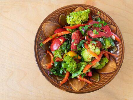 Top view on earthenware bowl with vegan vegetable salad mainly with broccoli, tomatoes and bell pepper. Stock Photo