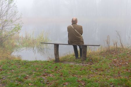 Senior man sitting lonely on a bench on riverside on misty autumnal monring Stock Photo