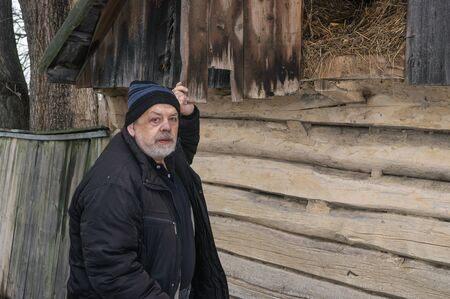 Outdoor portrait of Ukrainian old man standing near his barn with hay and looking with hope