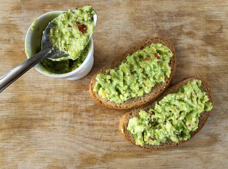 Top view on cut board with two  sandwiches  and teaspoon on small container with guacamole Stock Photo