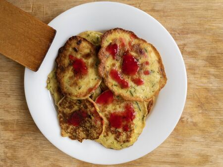 Top view on white plate with zucchini pancakes flavored with raspberry mash mixed with honey