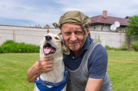 Outdoor portrait of two homeless fiends - dirty mature man and cute mixed breed dog that both are happy Stock Photo