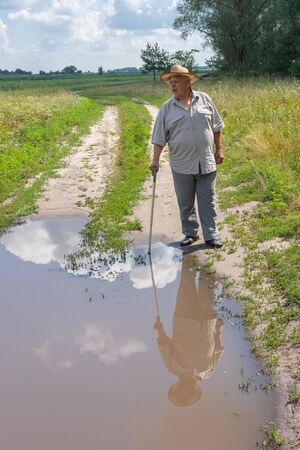 Senior man in hat standing near big puddle on the country road Stock Photo