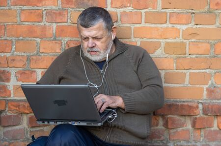 Nice portrait of bearded senior man working on a laptop and listening music while sitting against brick wall
