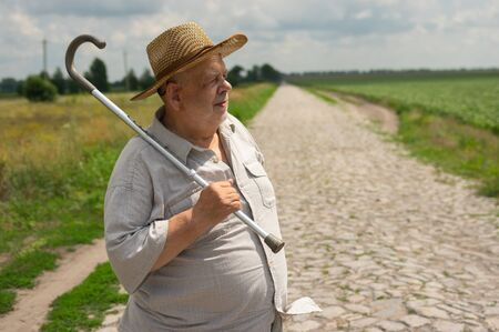 Nice outdoor portrait of Ukrainian senior farmer in straw hat standing on cobblestone road and taking walking stick