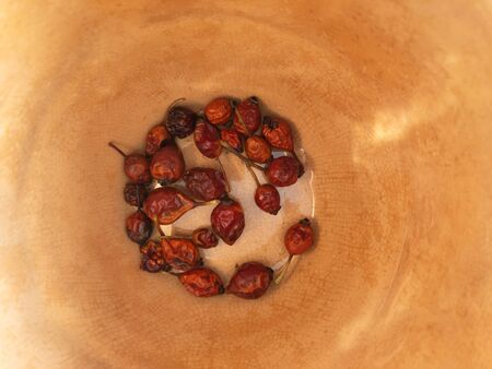 Top view on several dried rosa canina hips  lying on a bottom of earthenware pot