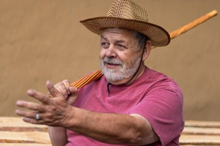 Bearded senior man in straw hat sitting against clay wall, gesticulating with left hand while holding wicker walking stick in right one on the shoulder
