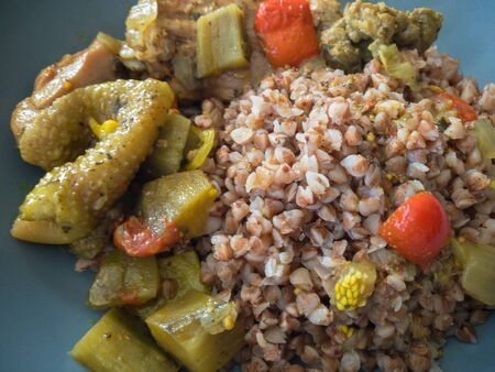 Top view on a plate full of buckwheat and stewed vegetables with duck meat