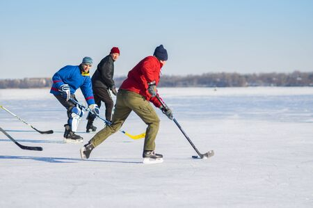 Dnipro, Ukraine - January 22, 2017: Group of different ages ordinary people playing hockey on a Dnipro river in Dnipro city, Ukraine 新聞圖片