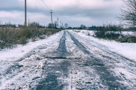 Winter landscape with an iced earth road in rural village Skelki, Zaporizhia Oblast, Ukraine