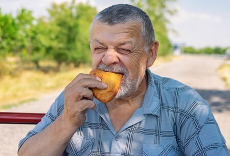 Hungry senior driver eating patty near his car on a summer road