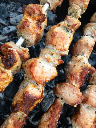 Close view on pork meat cooked outdoor on metal skewers