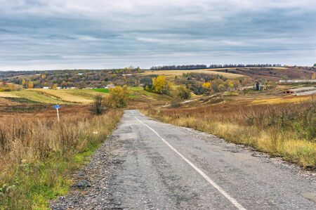 Landscape with an empty rural road at cloudy autumnal day in Sumskaya oblast, Ukraine