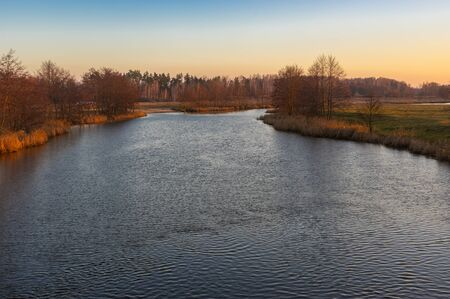 Pictorial evening landscape with Syrovatka river at sunset time, Sumskaya oblast, Ukraine