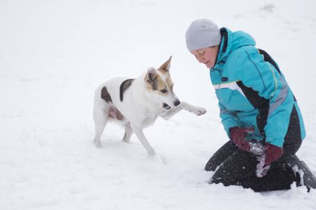 Mature woman playing with rope and mixed breed dog at winter season