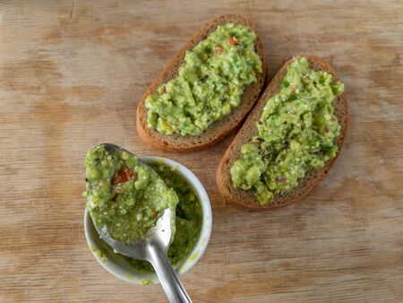 Top view on small cup and  spoon with guacamole next to sandwiches lying on a wooden table