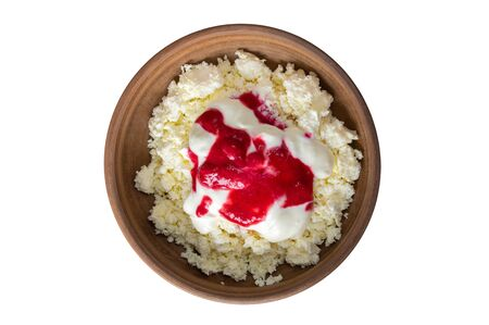 Top view on earthenware plate with cottage cheese with sour cream and fresh raspberry mash without stones isolated on a white background.