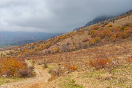 Autumnal landscape with an earth road leading to Valley of Ghosts when fog falls from the Demerdzhi mountain, Crimean peninsula