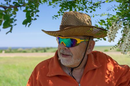Portrait of bearded Caucasian senior farmer wearing chameleon sunglasses and standing under acacia tree against green agricultural field