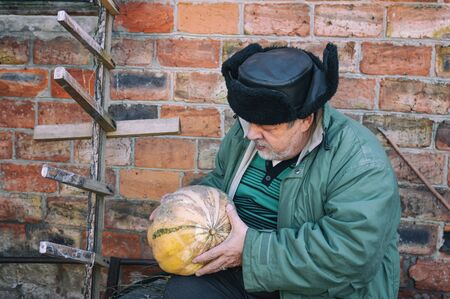Outdoor portrait of a bearded Ukrainian peasant taking pumpkin in the hands and looking at it while sitting against brick wall
