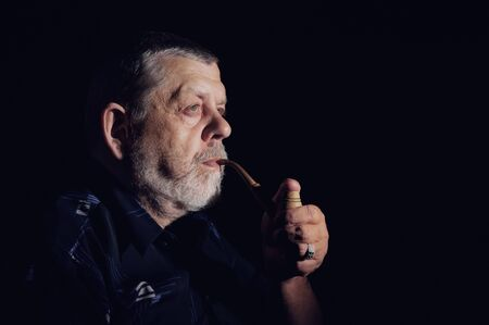 Nice dramatic portrait of senior smoking tobacco pipe in darkness