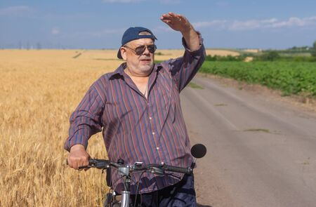 Outdoor portrait of a bearded, chubby senior man looking into the distance while riding on a bicycle on a country road