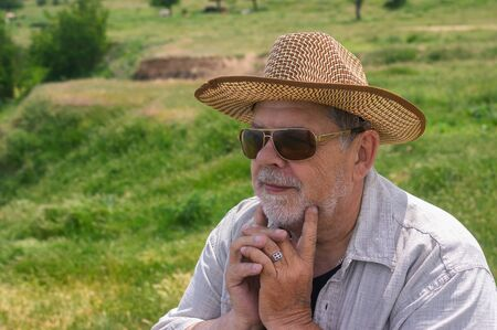 Outdoor portrait of happy Ukrainian countryman in straw hat and sunglasses against hilly spring pasture