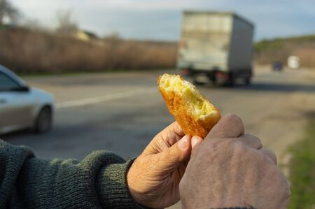 Hands of Caucasian hungry senior driver holding half of fried patty against road with cars