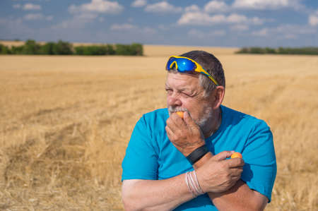 Outdoor portrait of a Ukrainian senior farmer in sunglasses eating apricots swhile sitting against an gricultural field