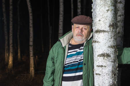 Close portrait of sad senior man leaned on birch tree in evening forest
