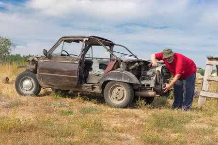 Senior man examining self-made car assembled from different ancient vehicles details Standard-Bild