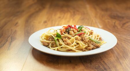 Spaghetti Stir Fried With Spicy Pork (thai lenguage Pad Khee Mao) in the dish on the wooden table, top view