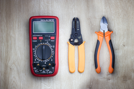 Different electrical tools on wooden table. Digital multimeter, cutting pliers and cable stripper. Top view. Reklamní fotografie